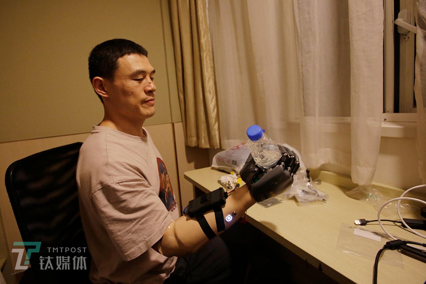 测试过程中,倪敏成用假手抓起一瓶矿泉水,通过长期合作和测试,这对他来说已经轻而易举。