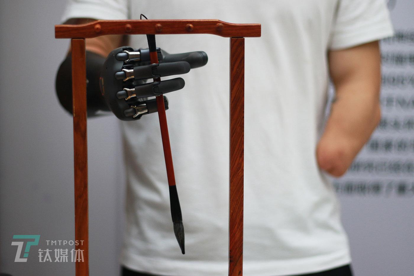 双创周活动现场,倪敏成拿起毛笔准备写字(写字视频见文章开头)。
