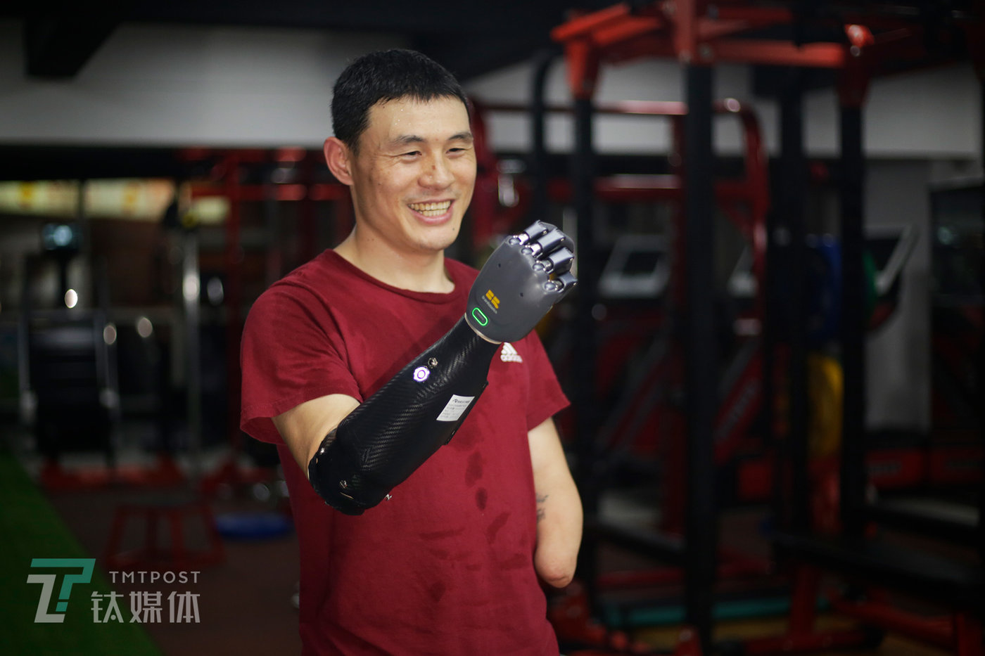 June 20, Jinhua, Zhejiang Province. Donning the BrainRobotics prosthetic hand, Ni Mincheng poses in his gym for a picture by TMTPOST Image.