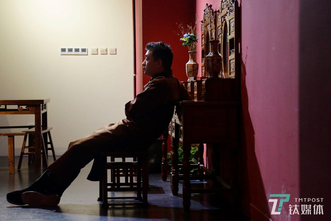 """7月10日晚,一场戏下来,实景演员张帅帅坐在门口休息。入职一年,张帅帅已经将""""皇都·沁血玉""""演过1000多次,他在游戏中扮演白天当医生、晚上开赌坊的""""门大夫""""。"""