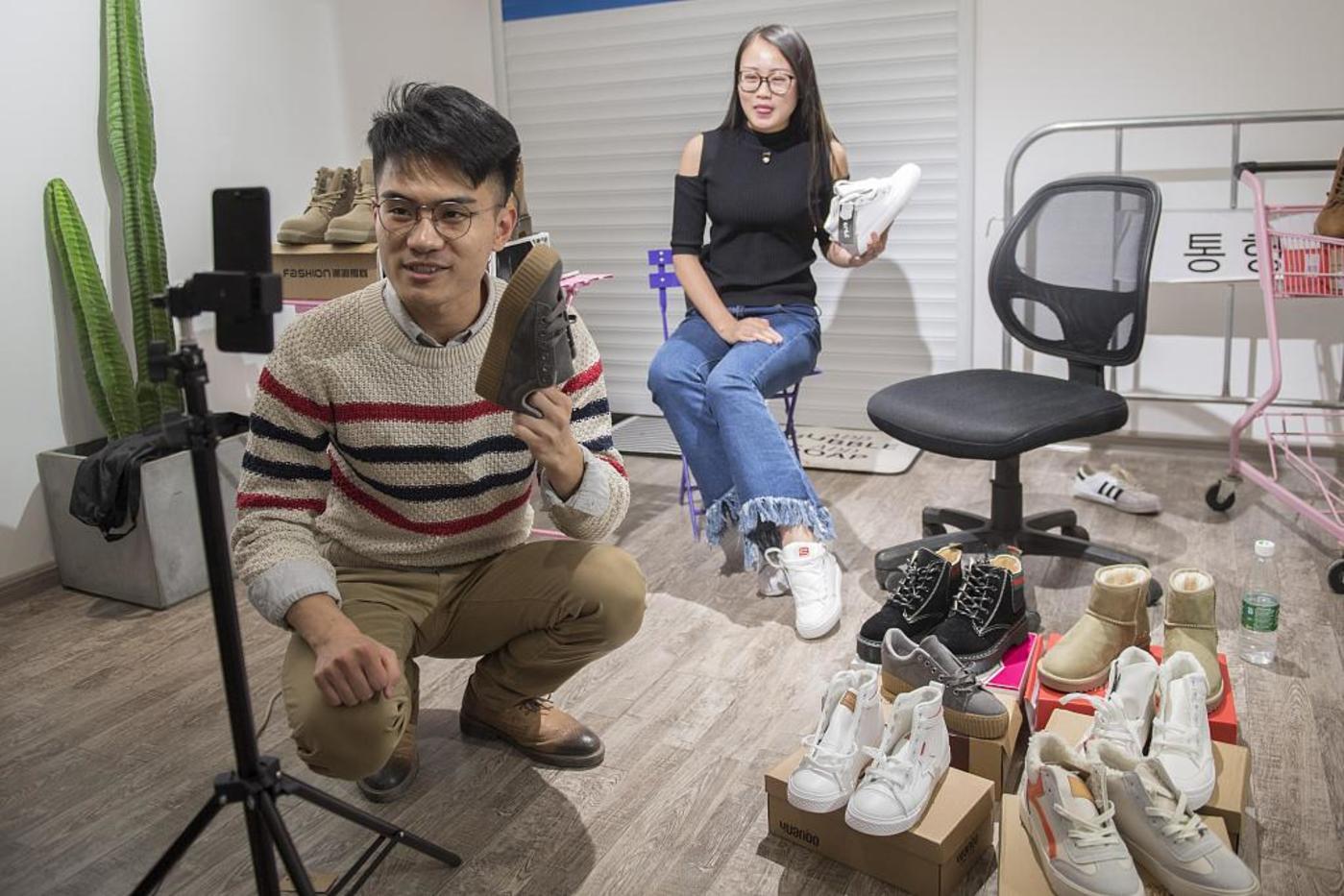 两位年轻人在直播中卖货。题图来源@视觉中国