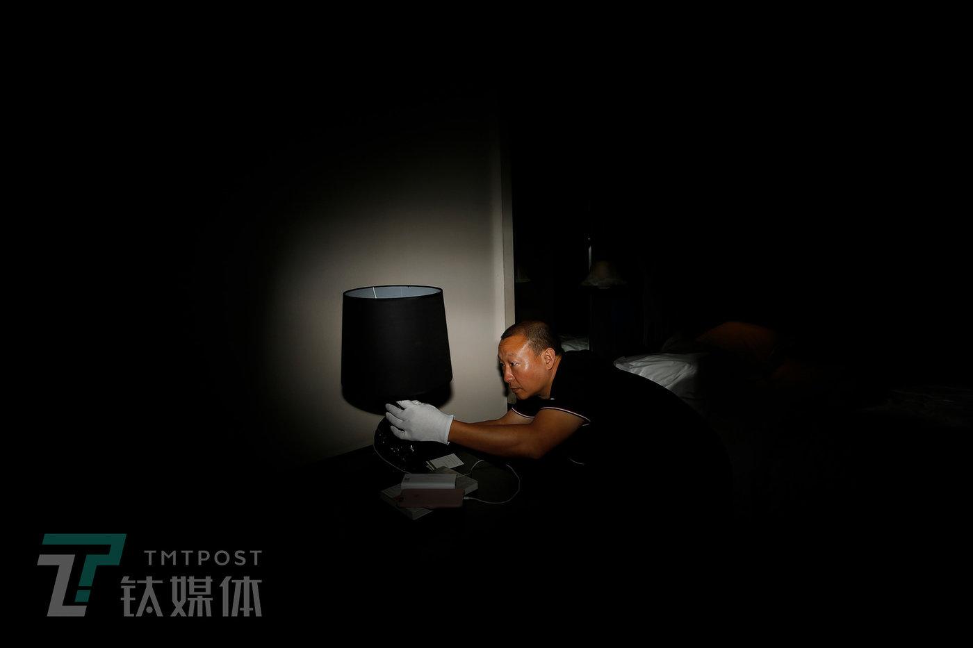 深圳某星级酒店,何志会在检查台灯。在采访过程中,他分别向钛媒体《在线》演示了如何检测办公室、酒店和排查车辆定位器。