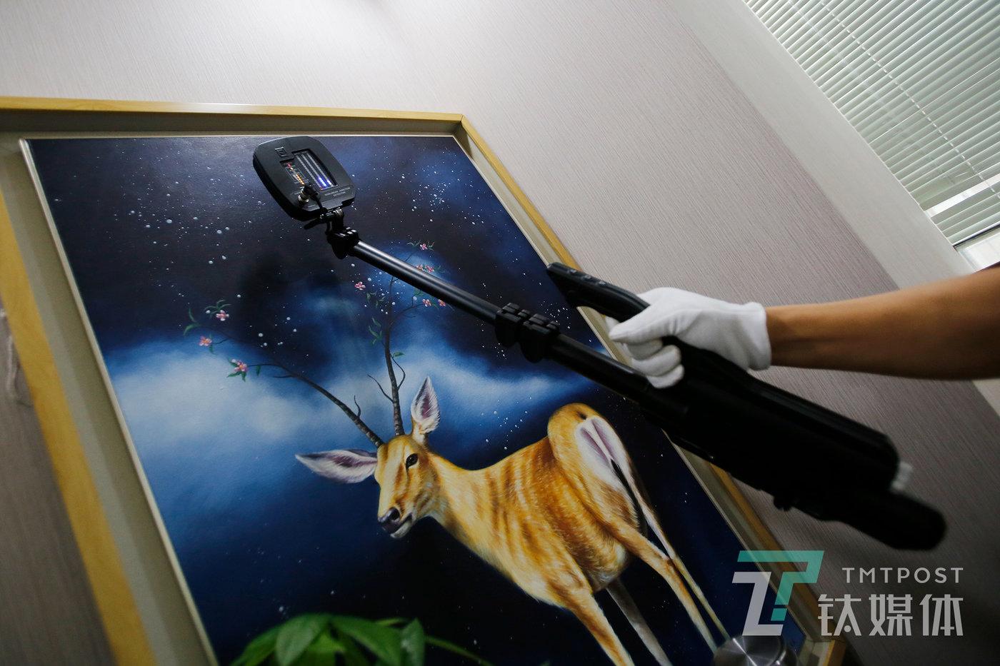 检测演示中,何志会使用节点探测仪扫描一幅装饰画。