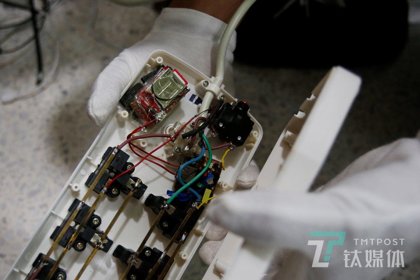 一个安装在插线板中的插卡式窃听器(左上),窃听器内有一个电话卡,它的工作原理跟手机类似,窃听者想要窃听的时候,需要拨通这个电话。