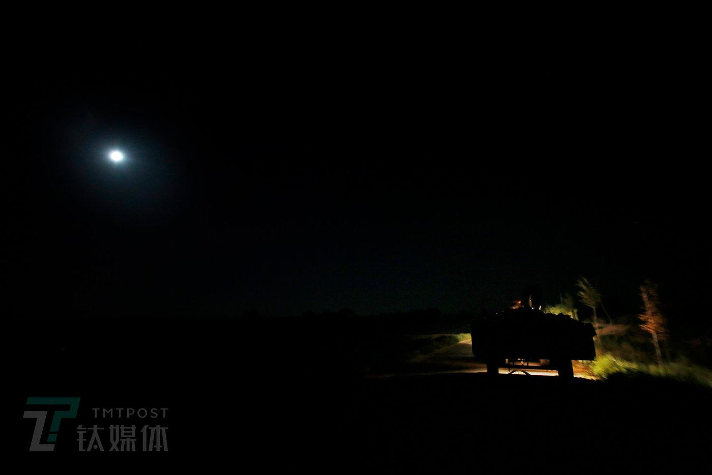 早上5点,气温只有10度出头,月光下,薛志明拉着一车瓜从村里赶往收成镇。从村里到镇上13公里,拖拉机满载有六千多斤,薛志明要开1个小时。他每天少则装2车,多的时候卖4到5车。