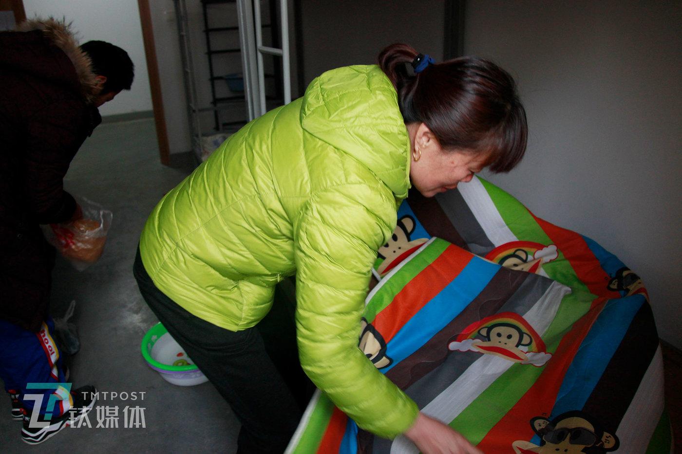 2019年2月25日,新学期开始,蒲公英广东快三新校区寝室,一位家长在帮孩子整理床铺。