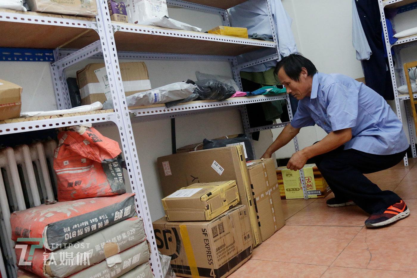 2019年9月7日,彭城父亲在自己值班的门卫室为业主取快递。