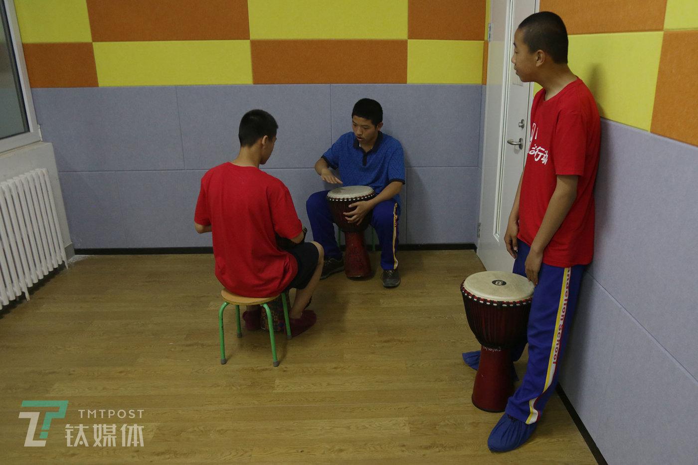 2019年5月9日,蒲公英中学,课外兴趣班上,彭城和同学一起学习非洲鼓。
