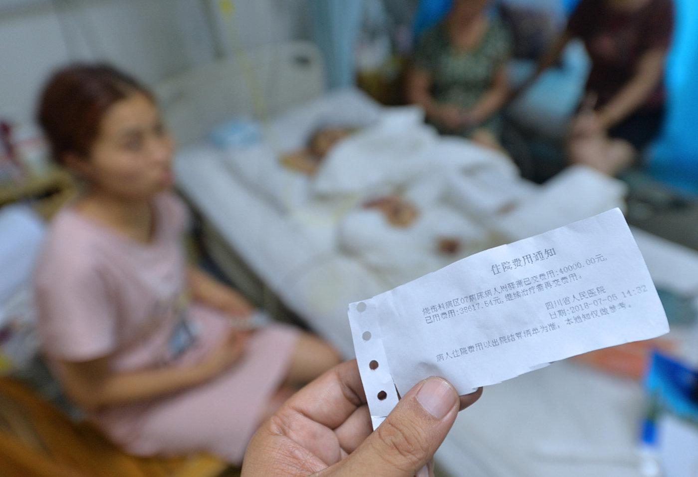 2018年7月6日,四川省人民医院烧伤科病房,面对医院刚发的缴费单,患者萧萧的爸爸周宇一脸愁容。图片来源@视觉中国