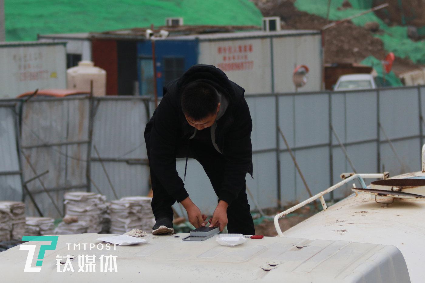 机械指挥官销售员陈兵在一台洒水车车顶安装智能终端。