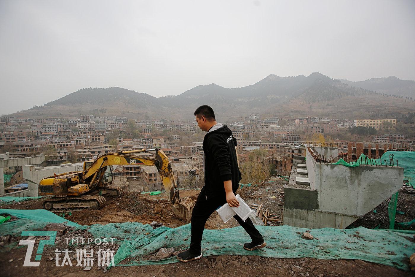 11月23日,某路桥工地,机械指挥官销售员陈兵准备走下护坡,为一台挖掘机安装智能终端传感器。