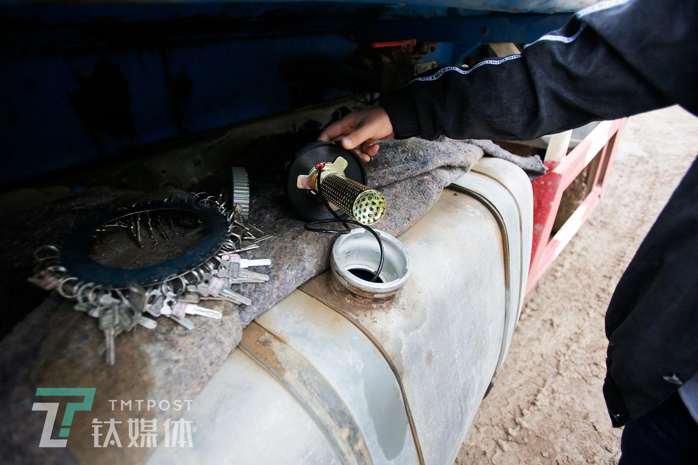 某工地,一名工作人员在给一台水泥罐车安装机械指挥官智能油箱盖。