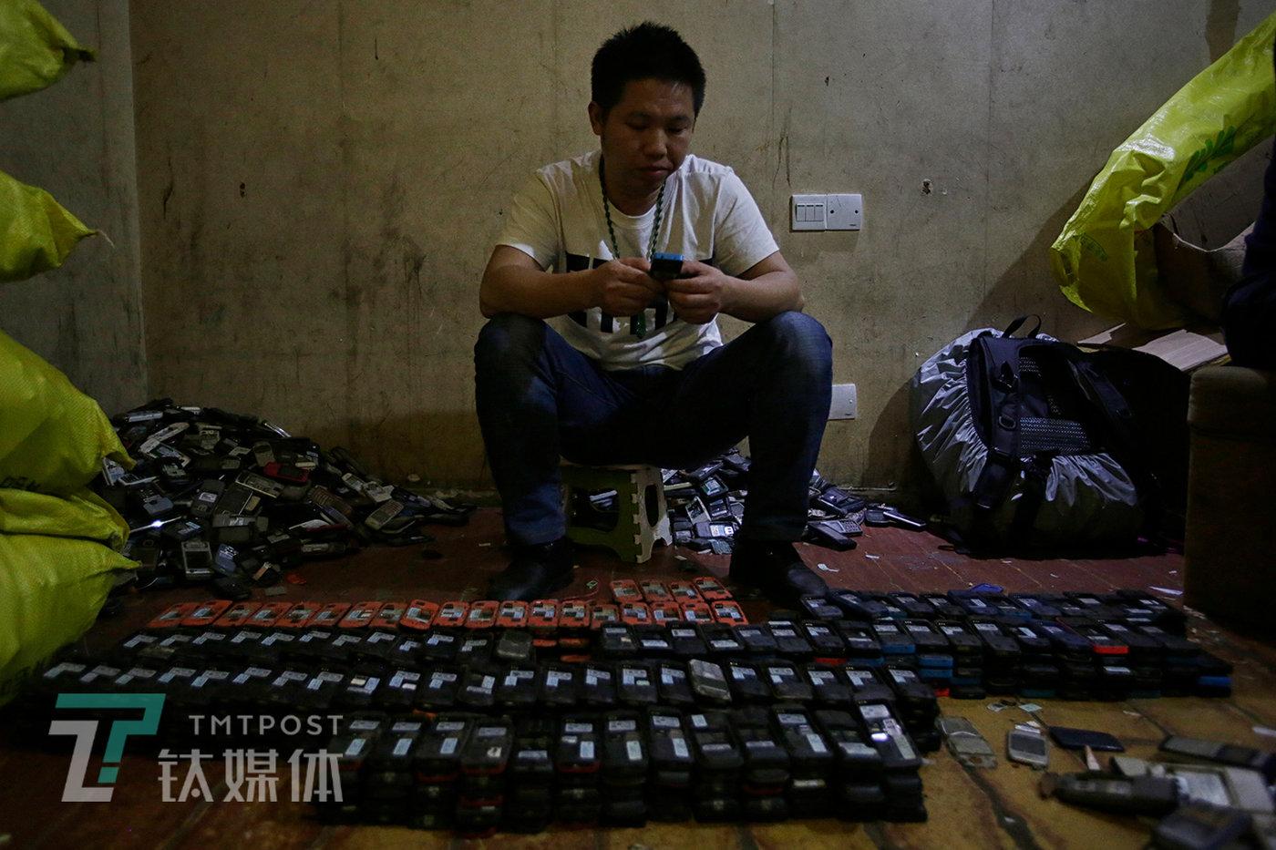 2月20日,深圳华强北附近某废旧手机回收市场,一名回收商在清点一批诺基亚功能机。这些手机中的一部分将被翻新转卖到非洲,另一部分将被送往贵屿等地用于提炼黄金。