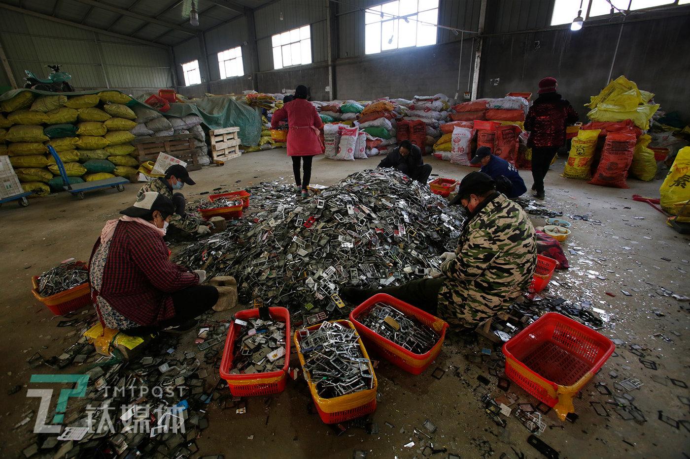 手机拆解厂内,工人在处理一批手机壳,这些手机壳将用于提炼金属锌。