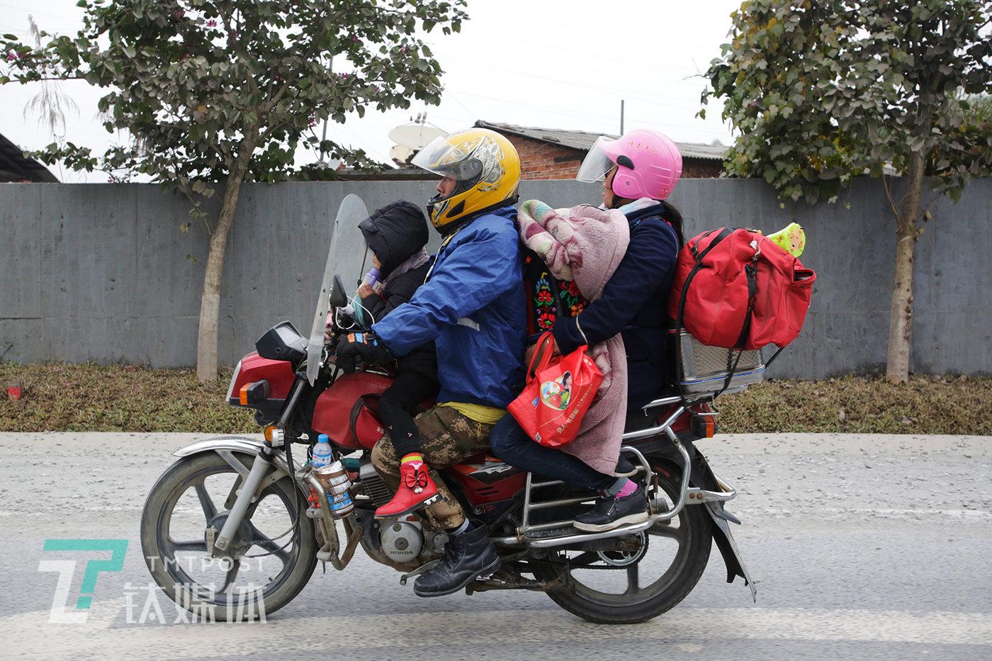 """1月26日,广西梧州,321国道上骑行回家的一家人。年初,我们跟随一名务工者从肇庆出发一路到南宁,记录了他的摩托回家路:《""""再累也要回家"""":17个小时行程700公里,一位骑摩托返乡人的回家路》"""