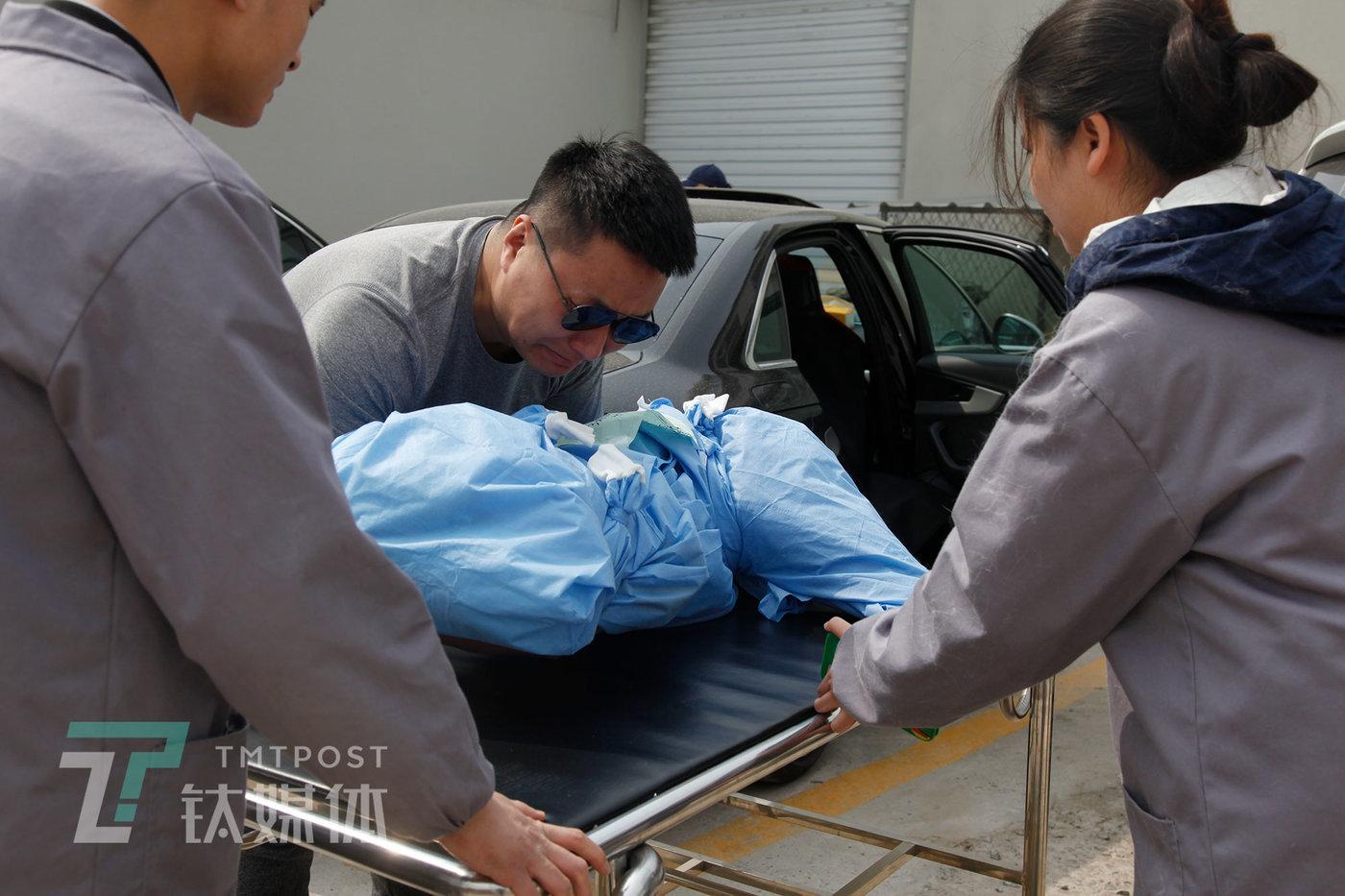 """3月19日下午,北京,狐狸(化名)将11岁大的金毛爱犬""""馒头""""从车上抱下,放到手推车上。"""