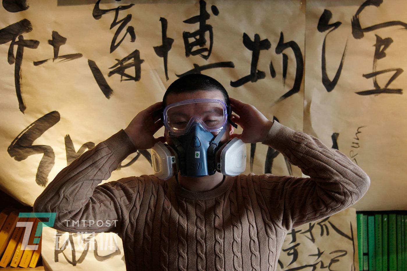 """4月14日,北京,""""社畜博物馆""""展览现场,主办方一名工作人员在展示一件社畜物品:防毒面罩。这件物品来自一名程序员,这名程序员说,公司要求员工在刚装修好的办公室办公,所以它买了这只面罩去上班""""表示抗议""""。"""
