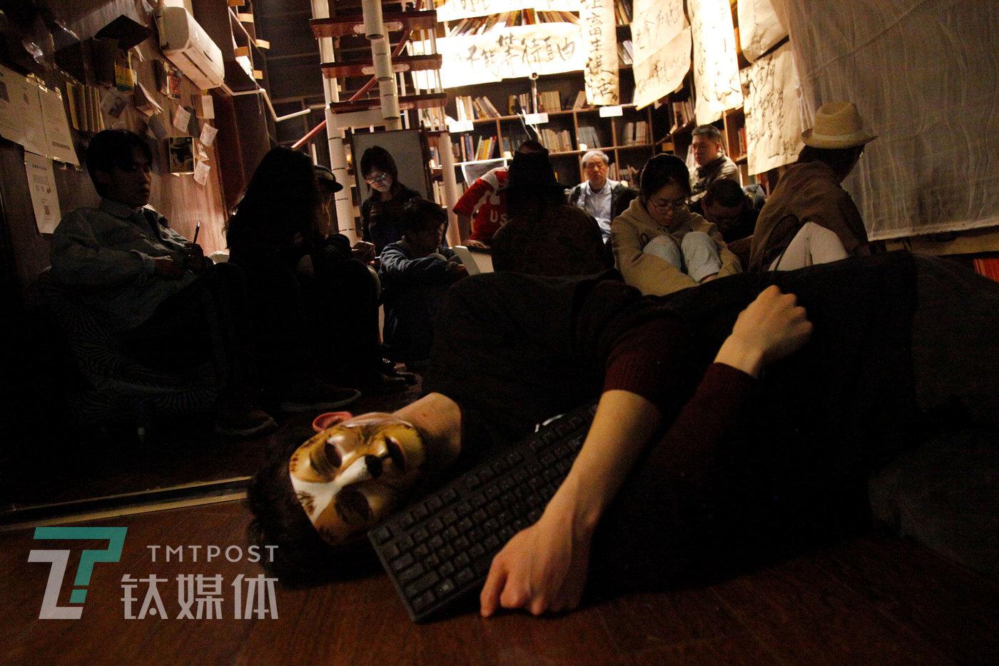 """""""社畜博物馆""""展览现场小剧场,一场有关""""过劳死""""的行为艺术表演:表演者扮演的程序员因加班""""过劳死"""",""""死去""""后仍抱着键盘。"""