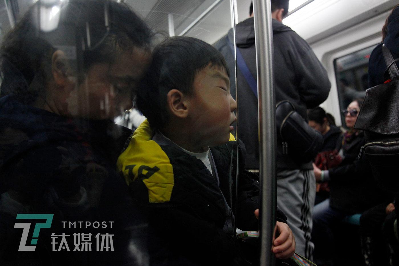 4月6日,北京,地铁上相依睡着的母子。