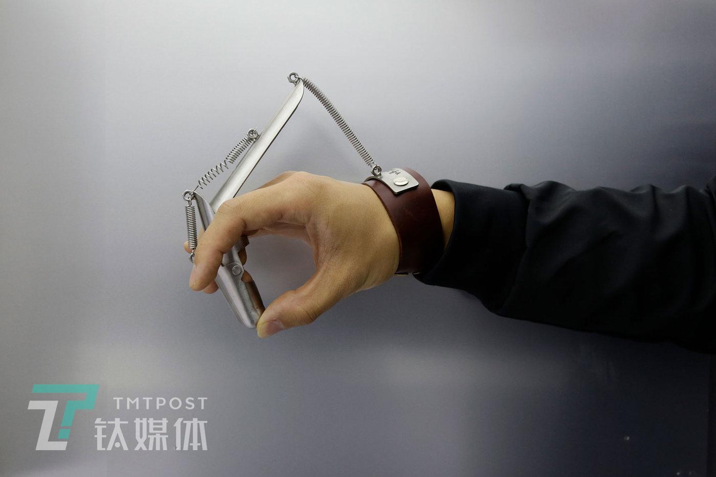 """11月8日,北京798艺术区,一场展览上,工作人员在演示手工耿作品""""弹脑瓜崩神器""""。"""