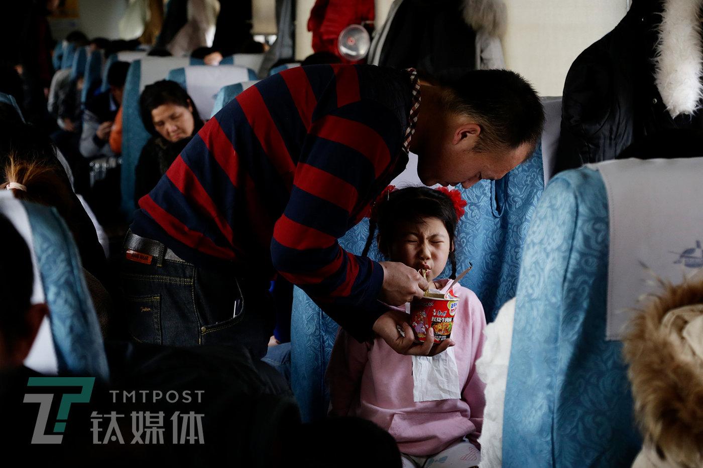 """别名男乘客在喂孩子吃泡面。列车上,方便面是一栽最常见的食品选择,有的乘客为了省钱,还本身带着塑料碗和筷子泡袋装泡面吃。餐车上吆卖的15元盒饭,在一些人眼中""""比较贵,且不值那价钱。"""""""