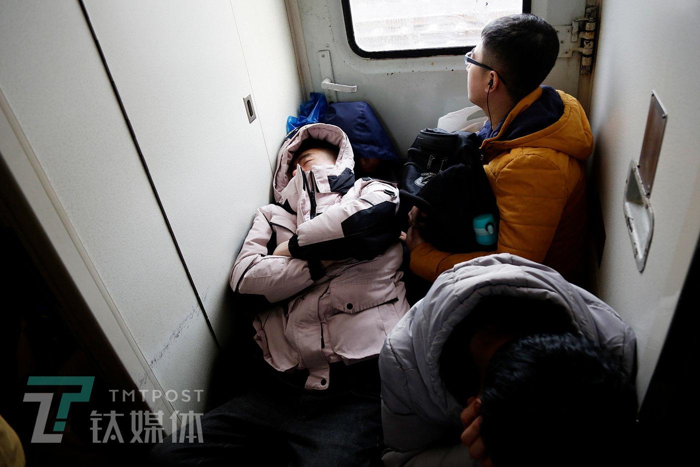 """列车车门边,4名乘客以分别姿势在休休。其中别名背部贴在车门上睡眠的乘客,成了另别名乘客的""""枕头""""。"""