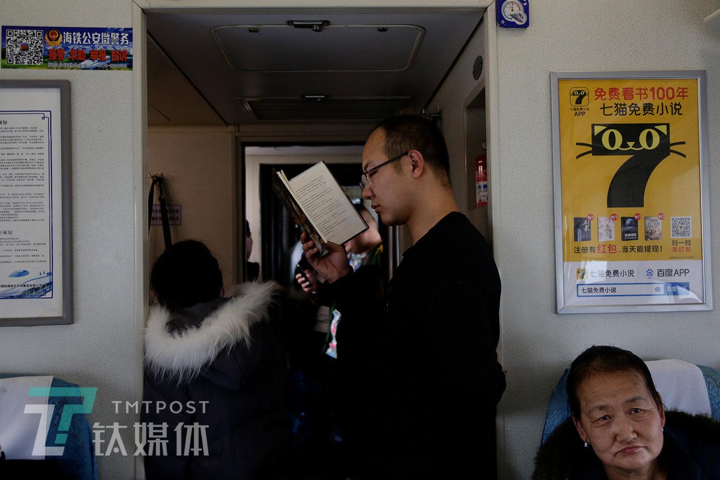 """别名乘客在看书。坐远程绿皮车回家,是一个专门""""难熬""""的过程。"""