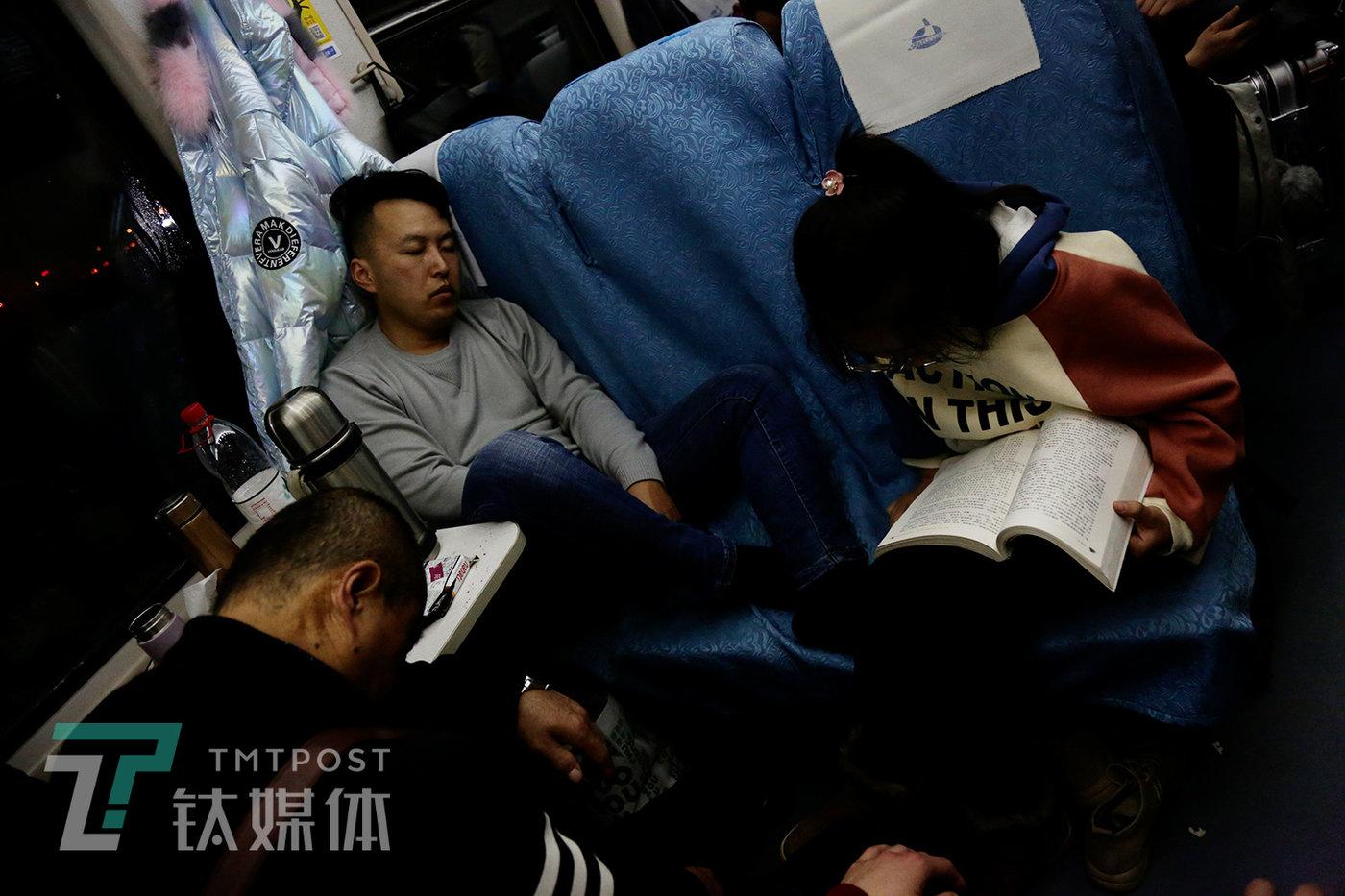 23:00,两位男乘客在休休,一位女乘客在看书。