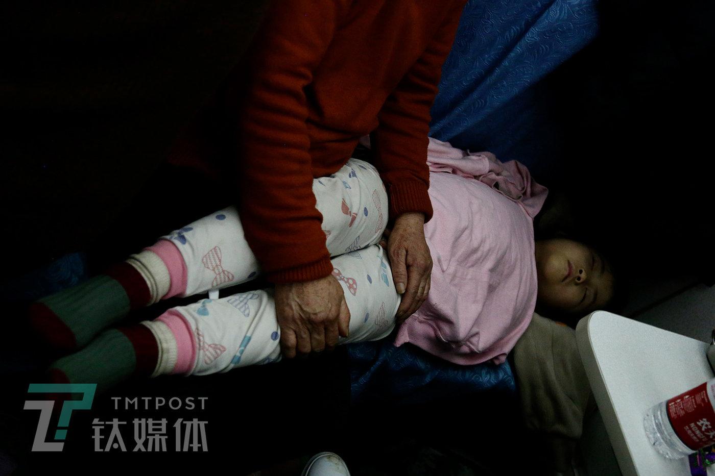子夜,硬座上,老人抱着熟睡孩子的双腿。