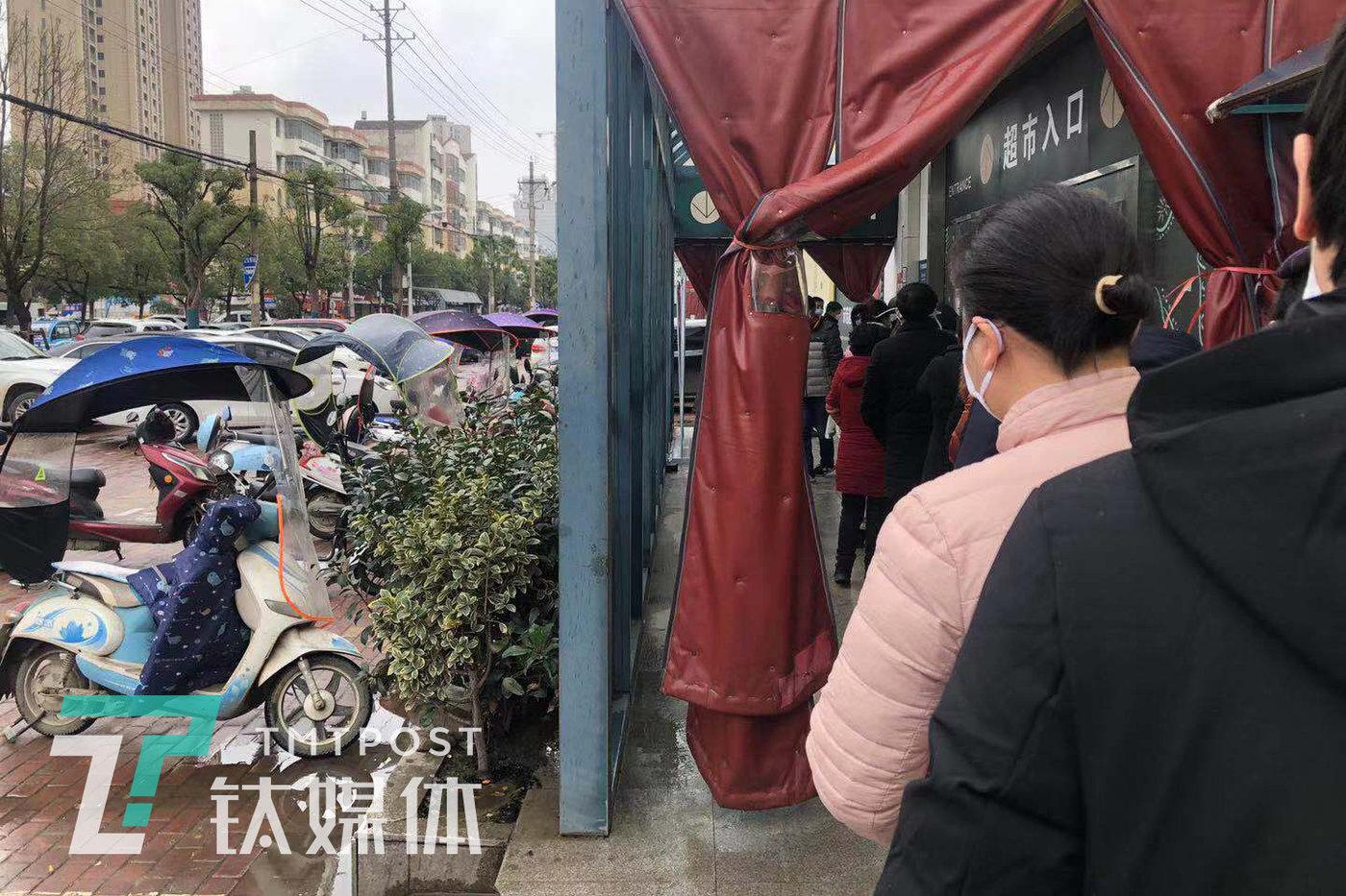 超市入口处,人们排队等待被测量体温。(受访者供图)