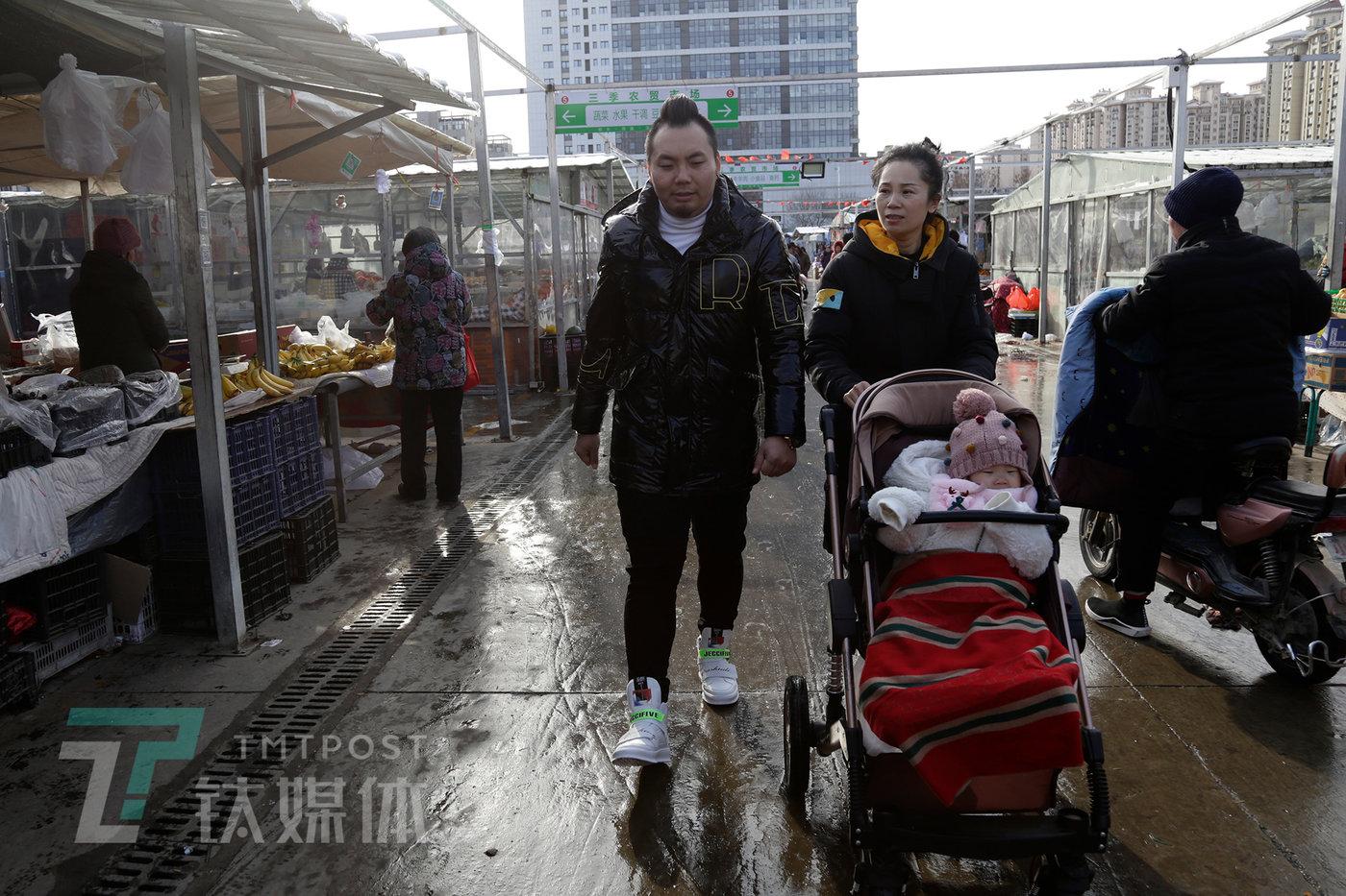 河北燕郊,阿绎和妻女儿在家附近菜市场买菜。
