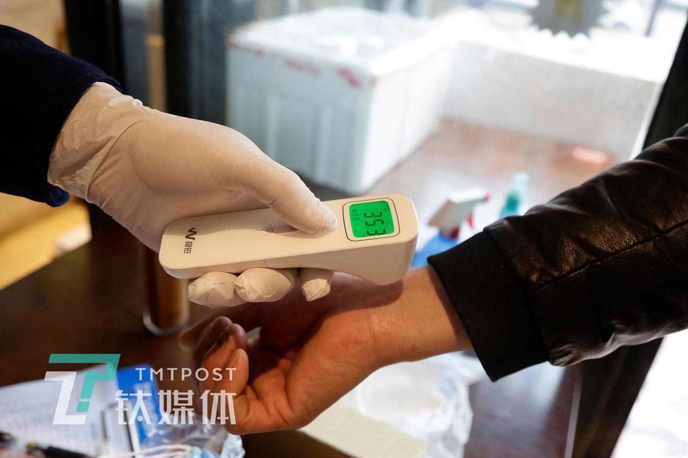 3月31日,北京,湘悦楼员工为进店顾客测量体温。