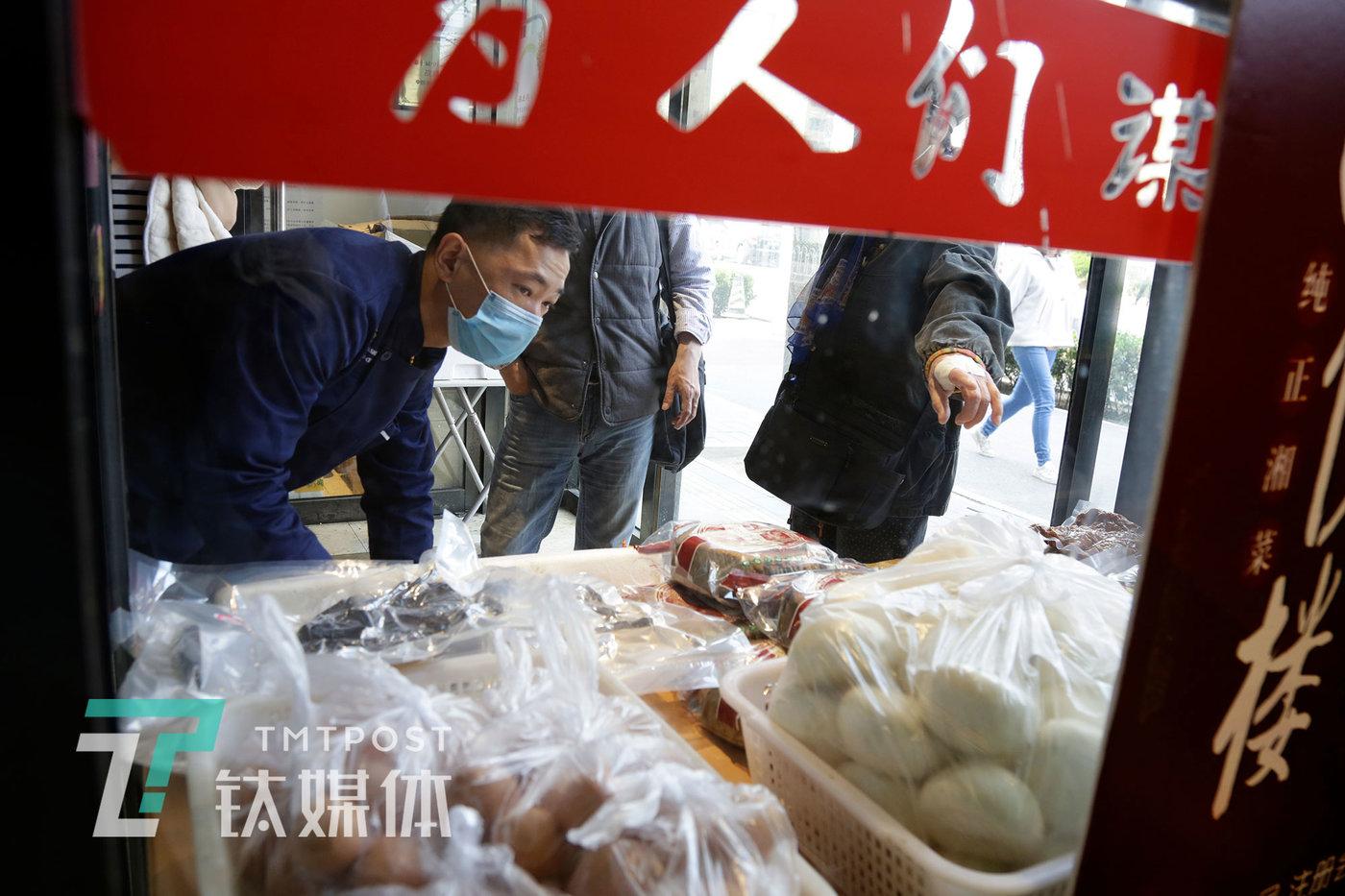 3月31日,湘悦楼员工(左)在门口卖菜。