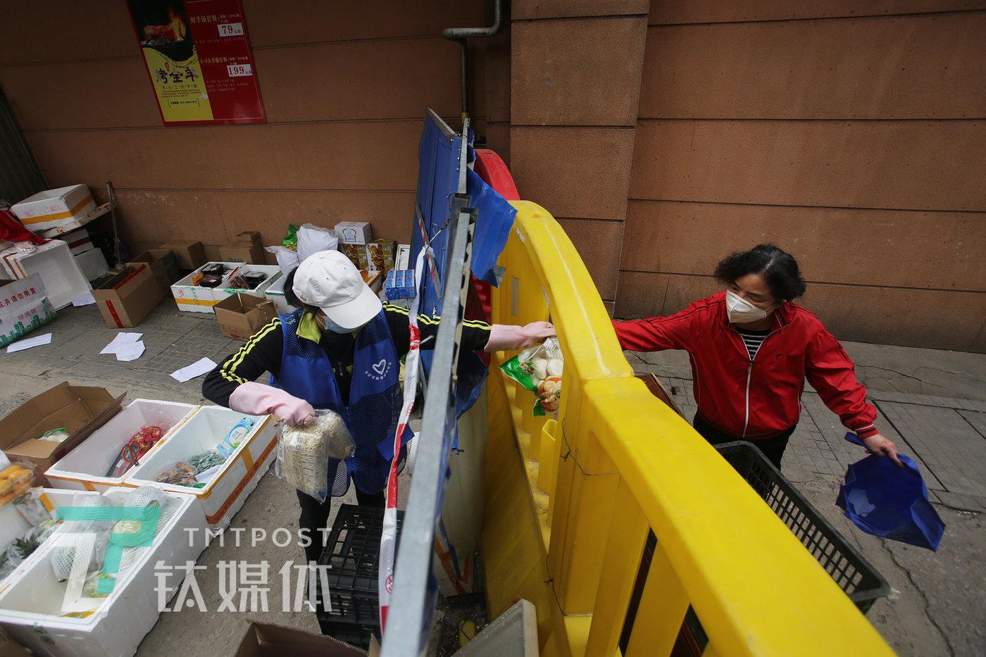 """4月10日,玫瑰园西村,一位居民(右)从围挡的""""洞口""""接过商品。"""