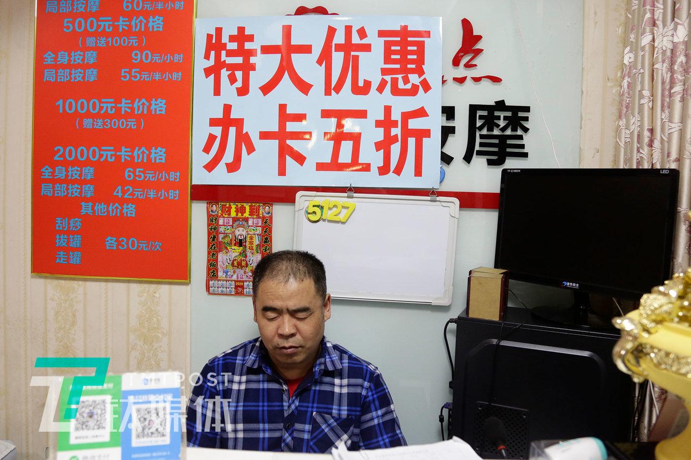 老李收银台,他身后的墙上是价目表和打折办卡的广告。