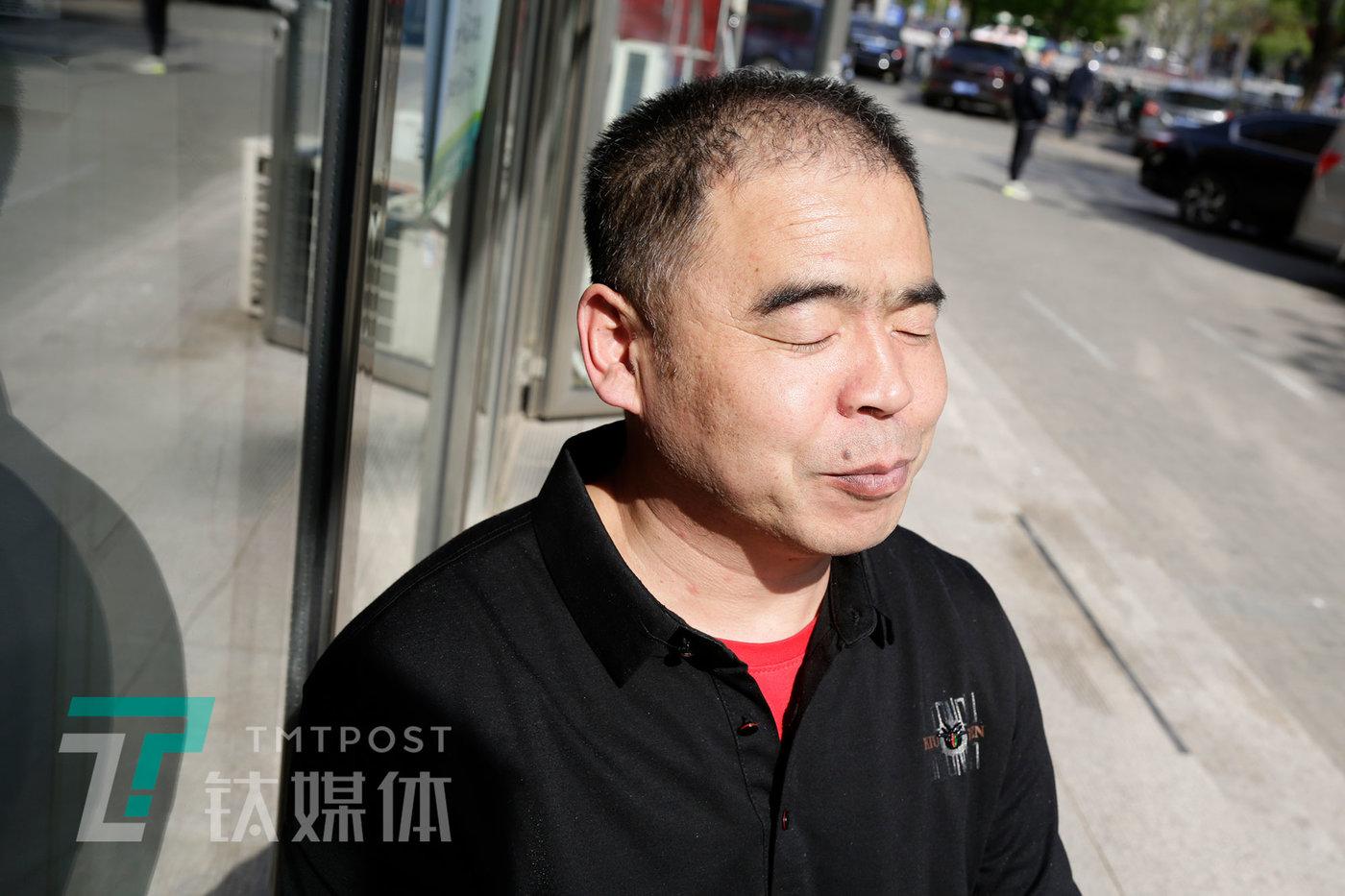 4月24日,北京,老李坐在店门口晒太阳。
