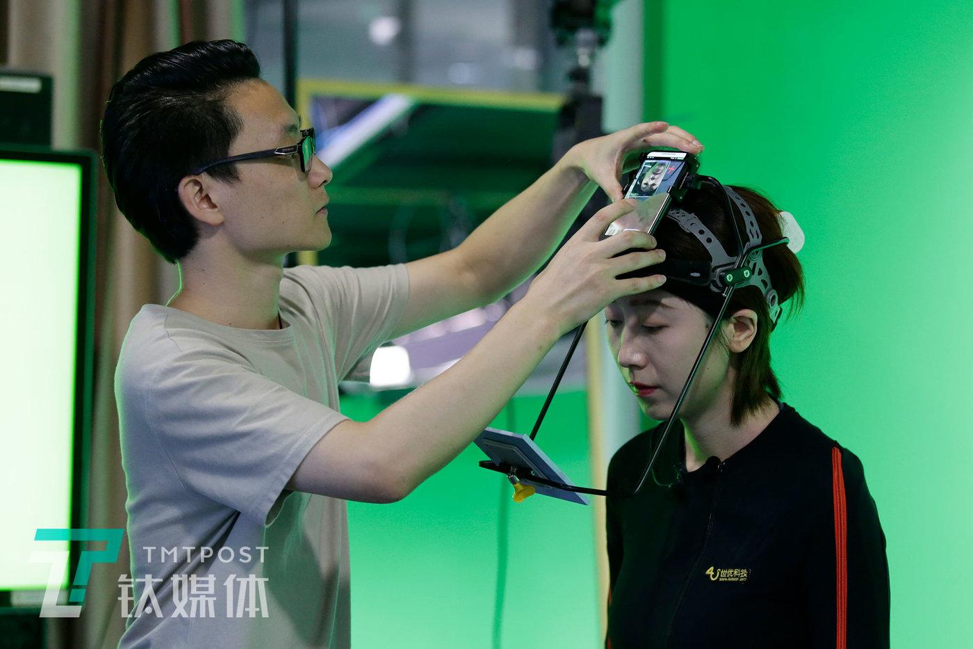 """录制前,工作人员为莫妮卡调试头盔,头盔重3斤多,用于捕捉表情,需要固定在头部,这重量让莫妮卡每次都感到""""头大""""。"""