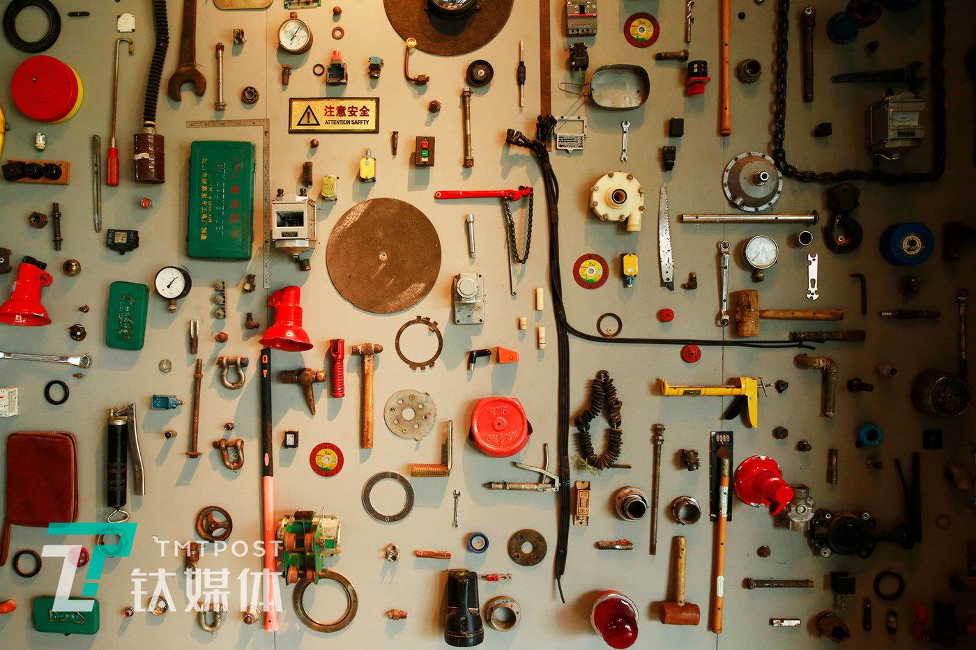 """首钢园区""""Shang Brew香啤坊""""艺术墙,墙上挂满原首钢工人们从全国各地寄来的劳动工具和零件"""
