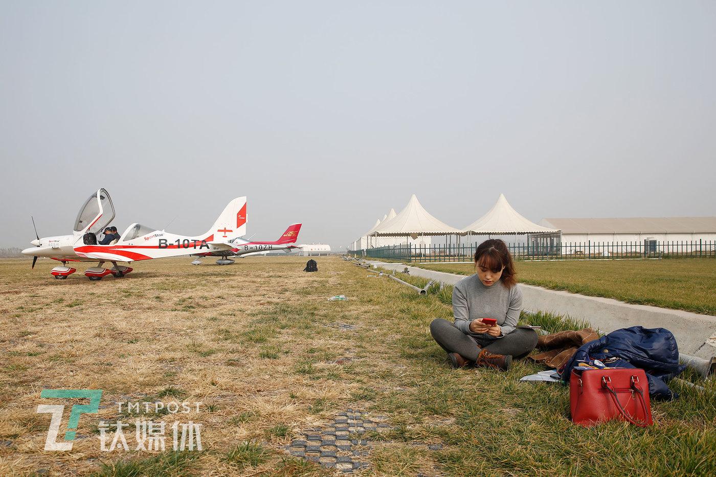 2020年11月16日,飞行练习过后,武凡辰坐在草地休息,闲暇时用手机处理工作事宜。