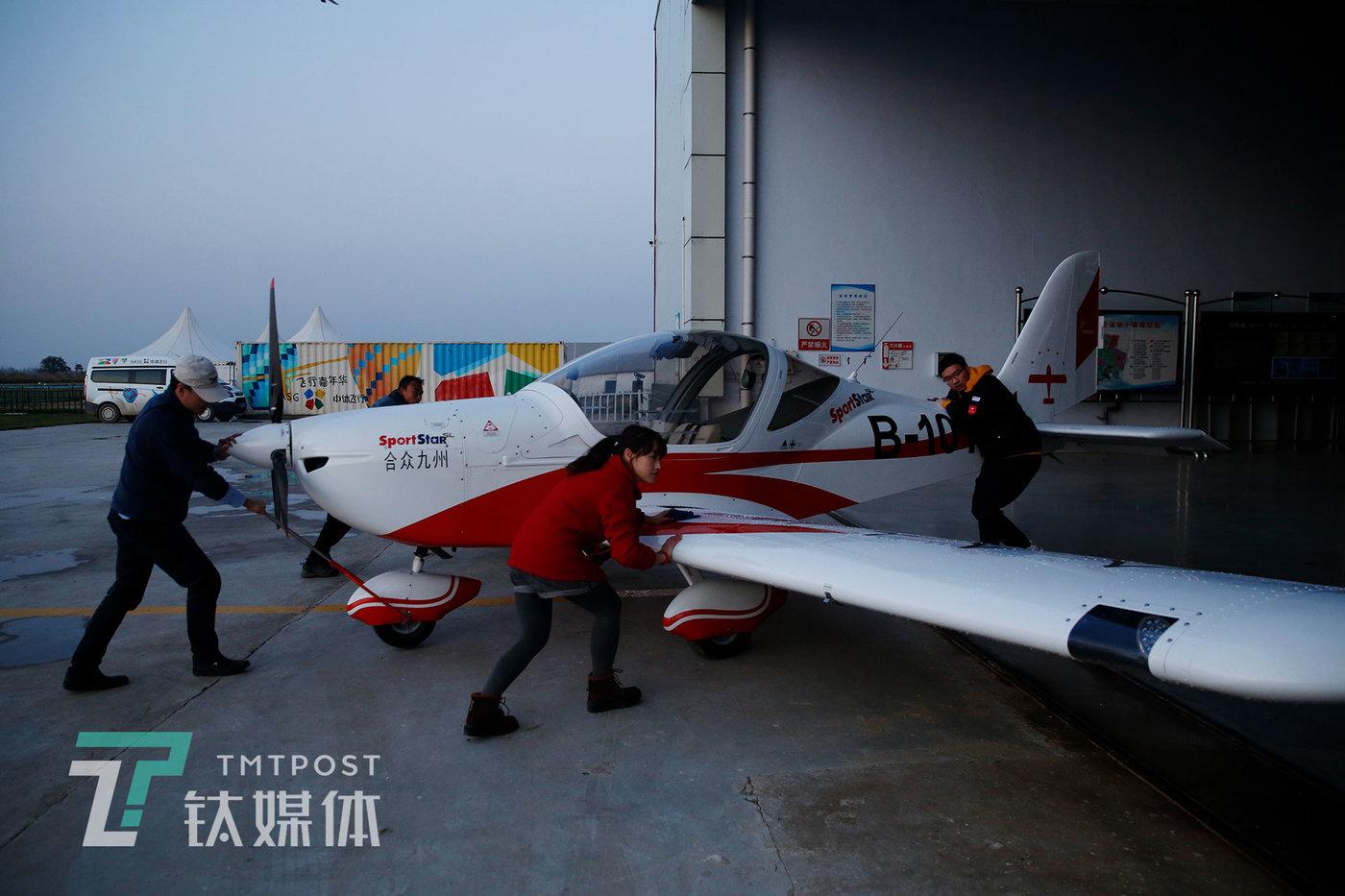 飞行训练结束,学员们一起将飞机推进机库。