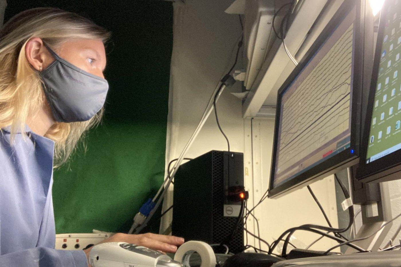 图 康科利正在观察一个沉睡参与者的大脑信号(来源:K. Konkoly)