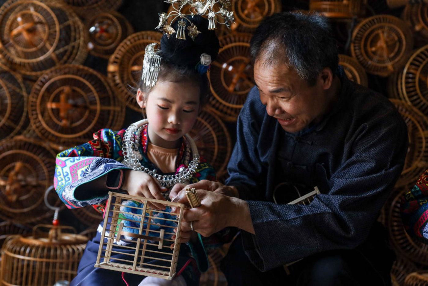 非遗传承人杨雪亮(右)在指导一名苗族女孩制作鸟笼