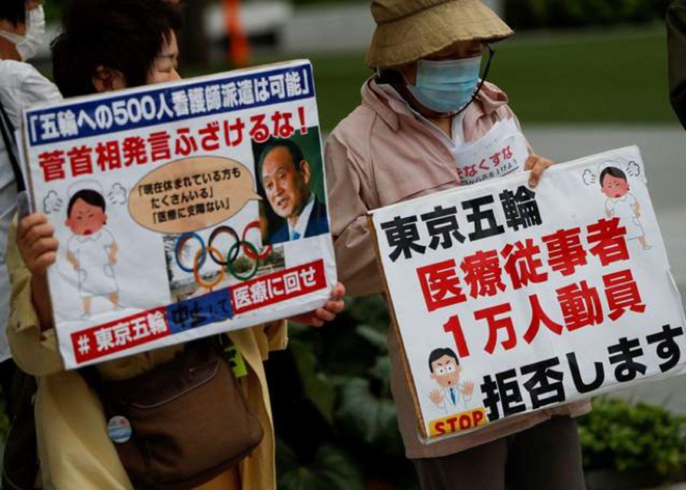5月18日,东京奥委会大楼外,日本民众举起标语抗议举办奥运会