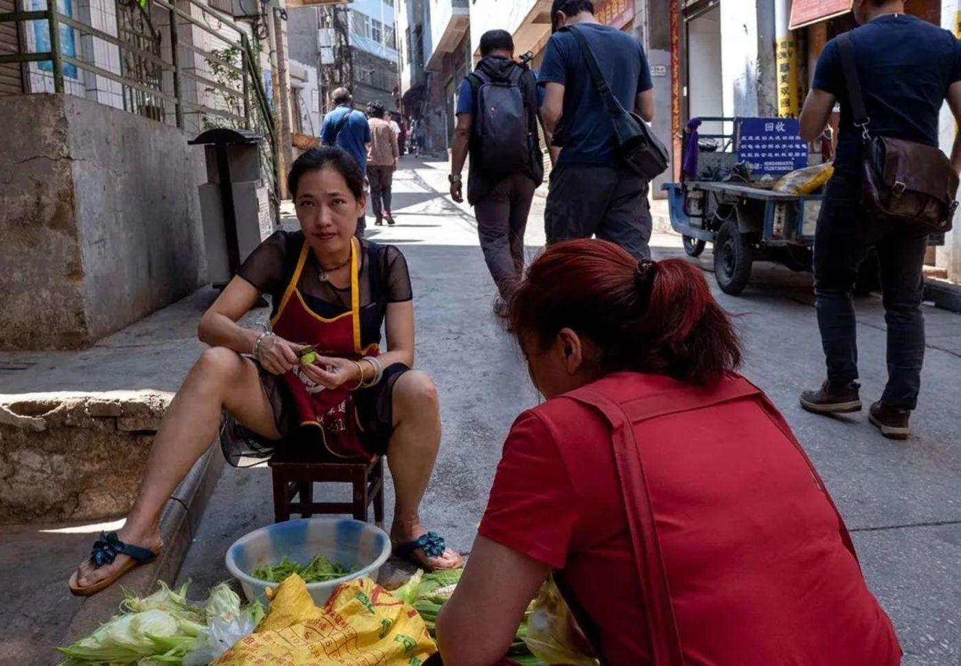 个旧街头准备晚餐的妇女,图片来源:沈少雄 摄