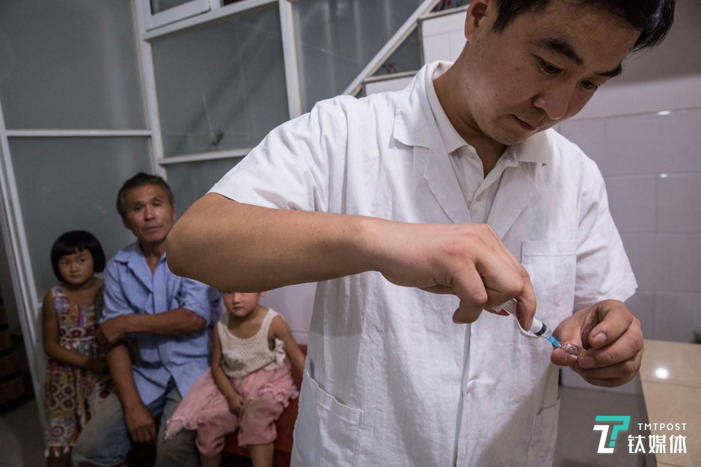 乡村医生。河南新乡,乡村医生师进峰准备给一名患感冒的留守儿童打针。