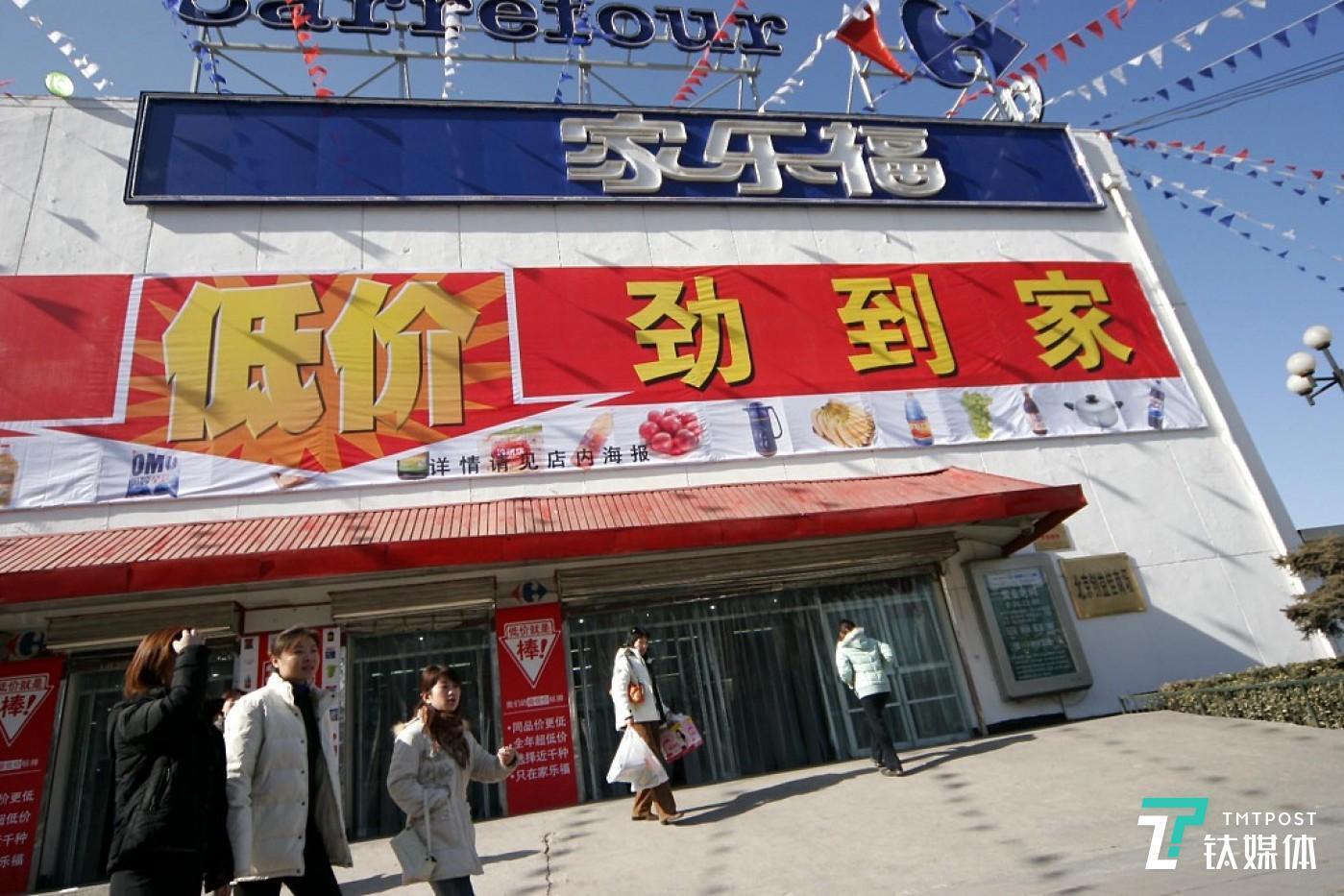 2006年2月20日,北京一carrefour家乐福超市低价劲到家的广告下顾客正经过