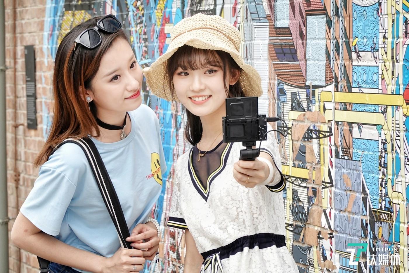 模特小姐姐手持索尼黑卡RX100M6相机自拍