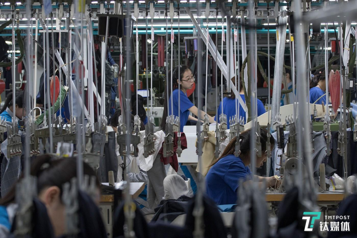 悬挂的青春。山东青岛,酷特智能车间的西服定制生产线,年轻女工在挂钩间工作。